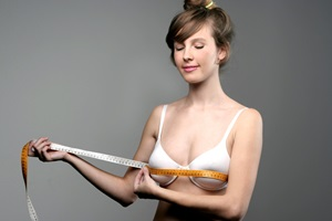 A woman measuring the size of her breast with a measuring tape.