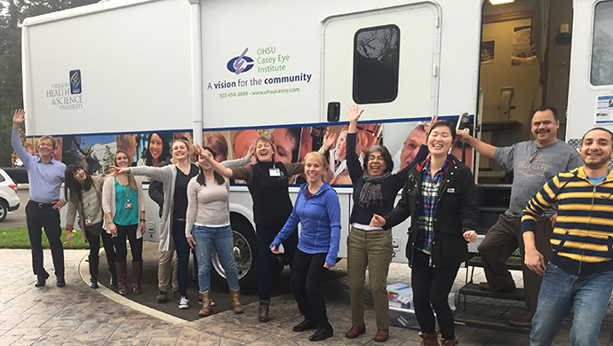 Volunteers do a fun pose in front of the mobile clinic.