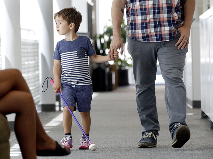 A young boy with inherited retinal disease walks with his dad. He was treated with the first FDA approved gene therapy Luxturna.