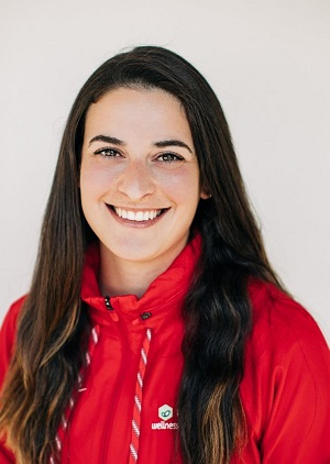 Gabi Slavid from march wellness & fitness center with long brown hair and wearing a red jacket.