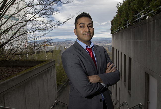 A doctor standing outside in an OHSU courtyard that overlooks East Portland.