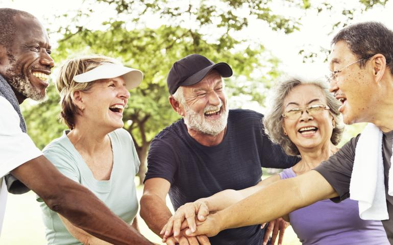 Diverse group of older adults laughing and holding hands.