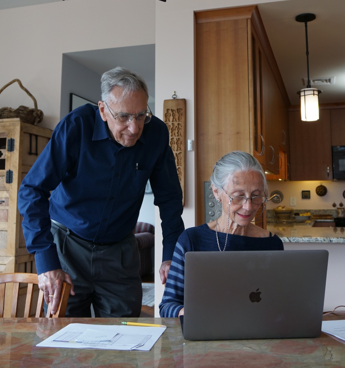 Two research participants using a computer in their home