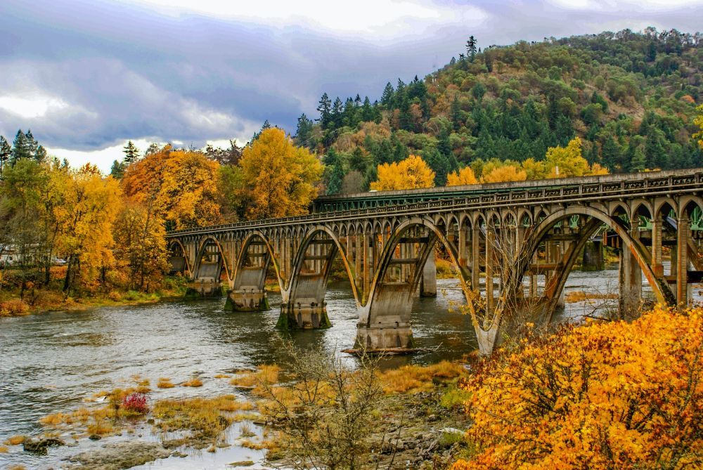 Arch bridge across a river in Oregon in the fall.  Foliage on surrounding trees is yellow and orange.