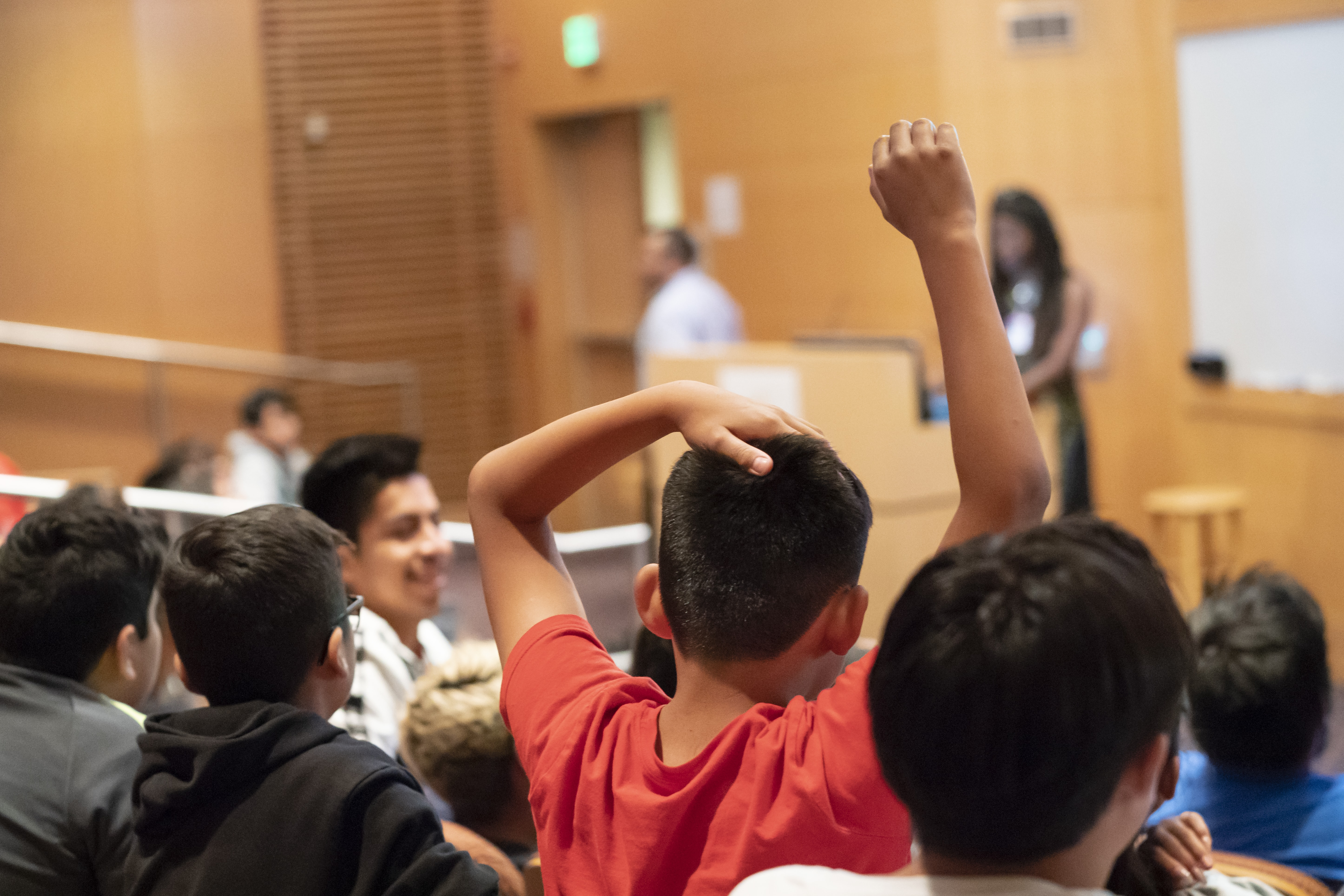 Student raises hand while listening to presentation about neurology