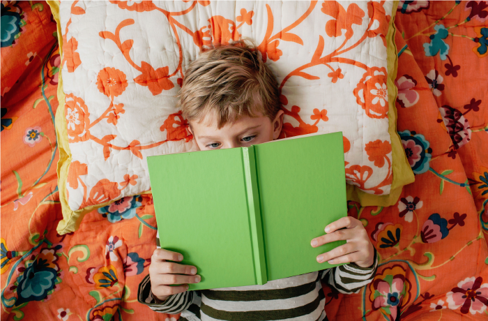 Photo of a child reading a green book on an orange pillow and blanket | Health Magazine Fall 2019