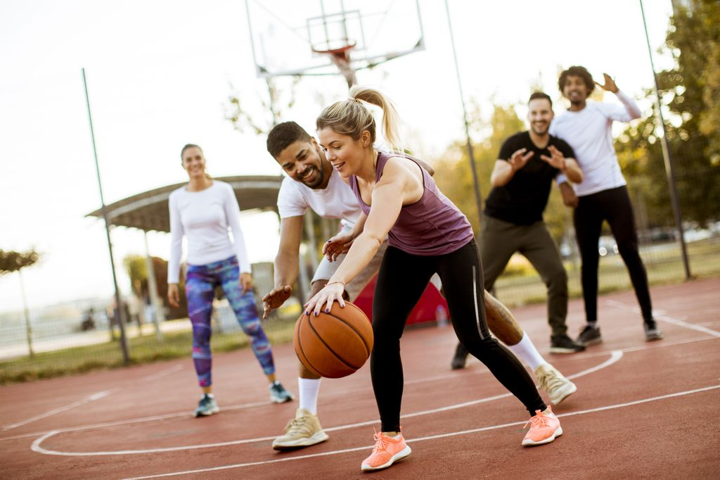 Stock photo of a group of adults playing basketball outdoors