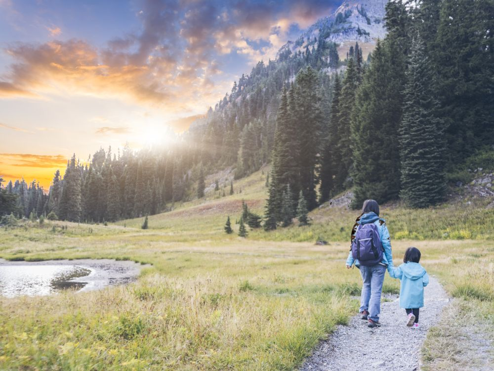 Mother hiking with young daughter on a trail with a view of Mount Ranier.