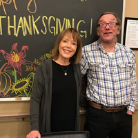 Kate with her husband in front of a 'Happy Thanksdgiving' chalkboard drawing