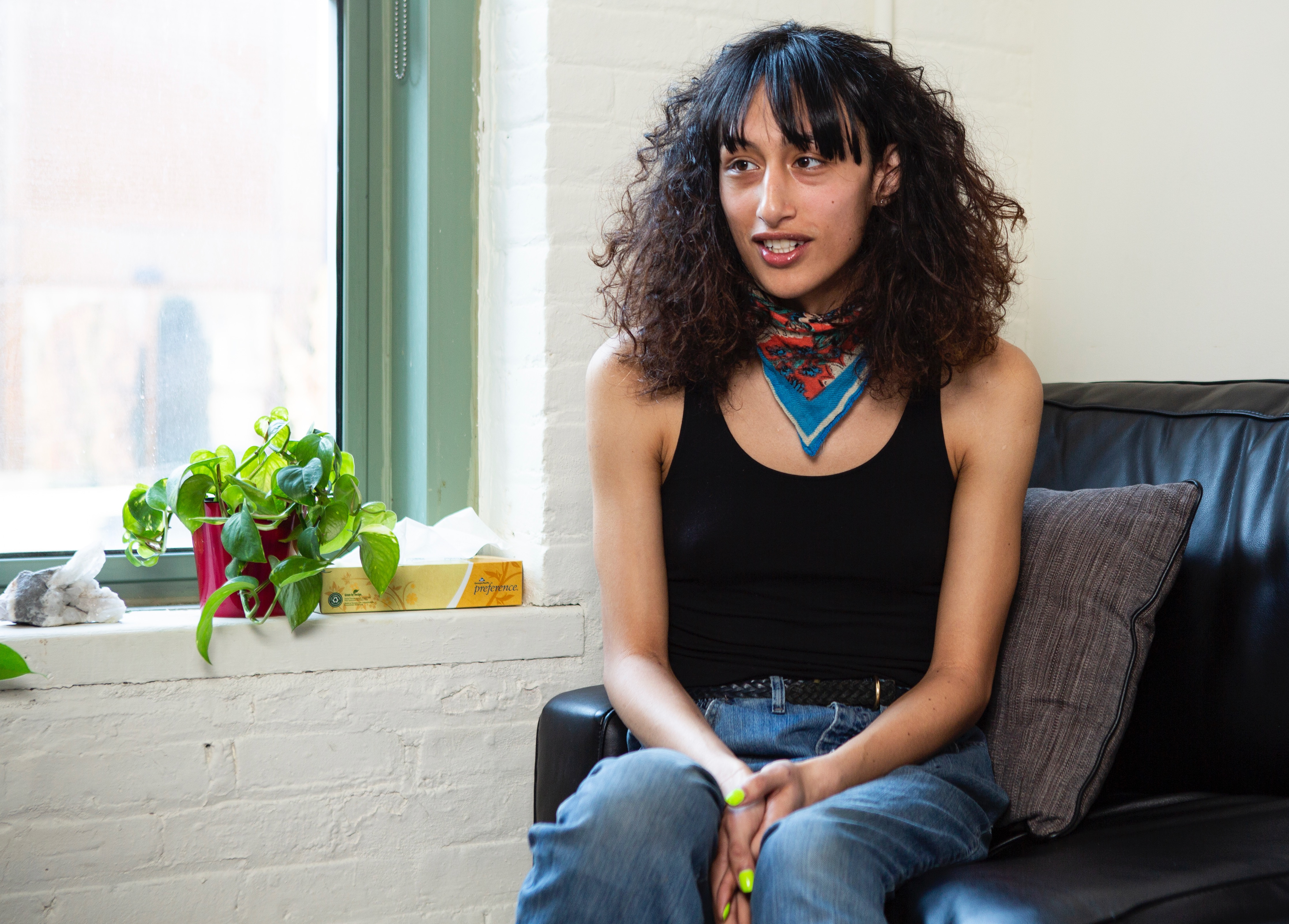 A transgender woman sitting on a therapist's couch and smiling