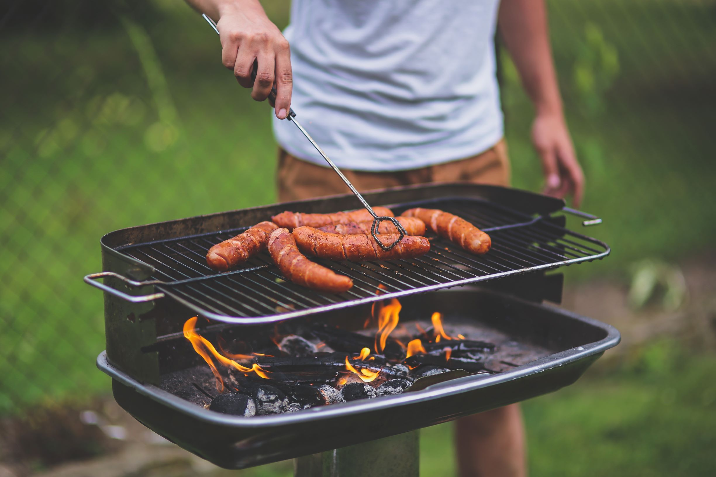 man grilling hot dogs over charcoal grill