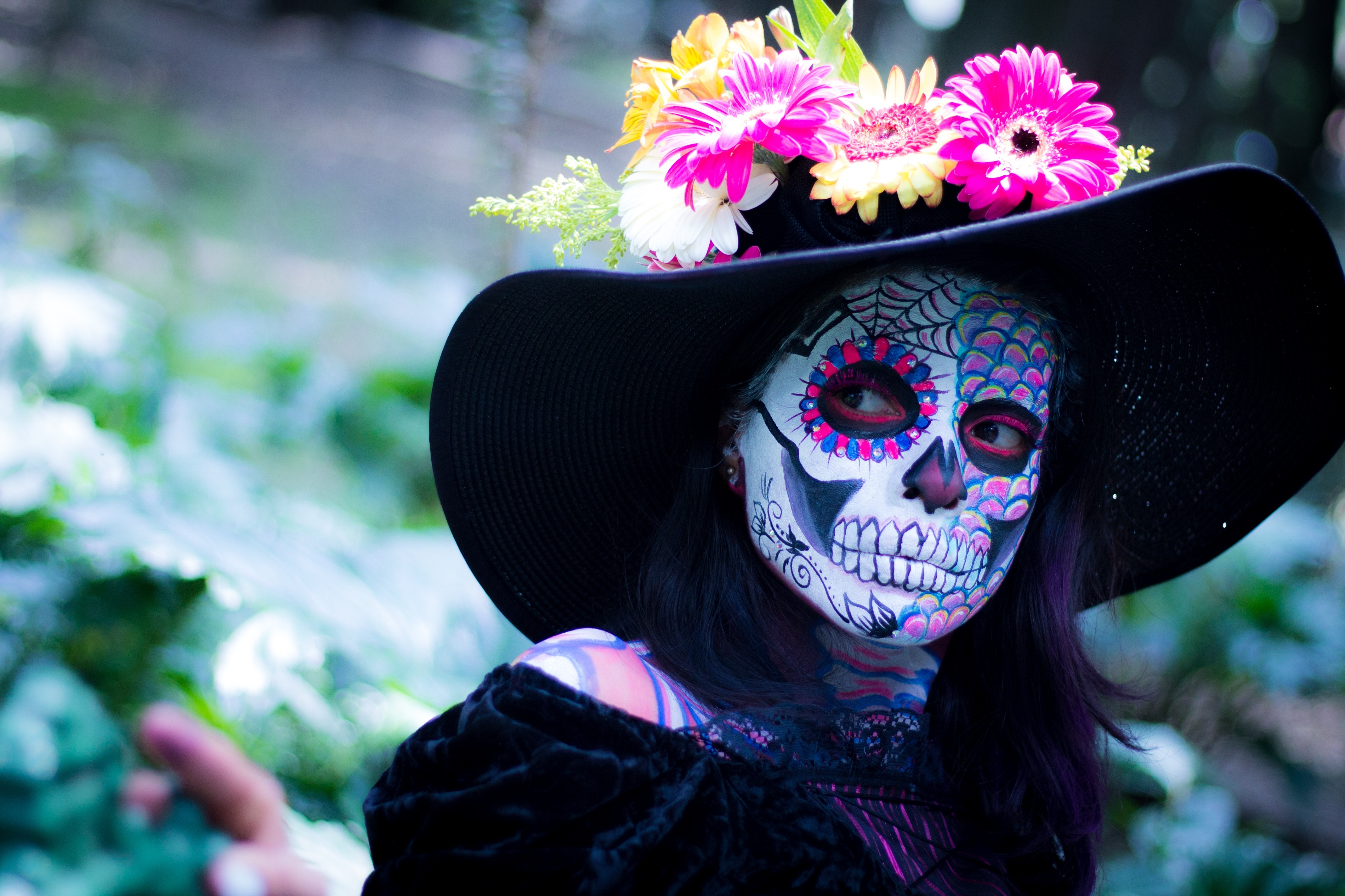 woman dressed in costume and full makeup for halloween as day of the dead