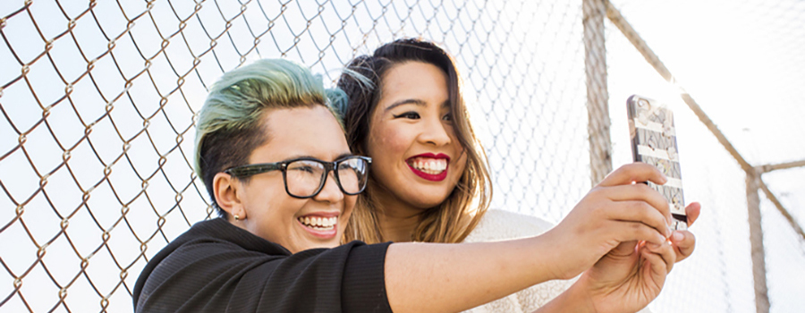 Photo of two smiling people taking a selfie outside by a fence