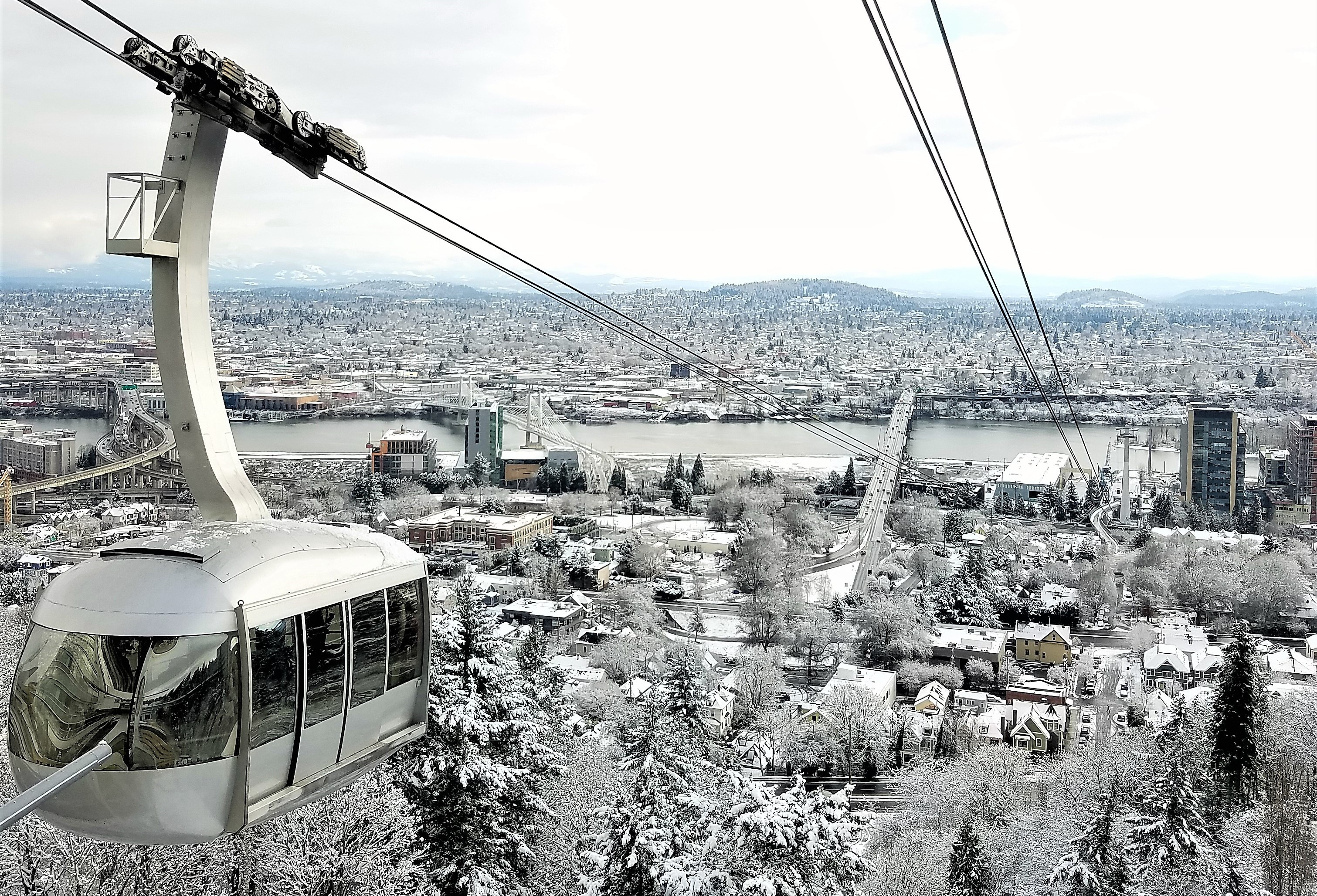 Portland Aerial Tram arriving at the upper deck with a backdrop of the entire city covered in snow.