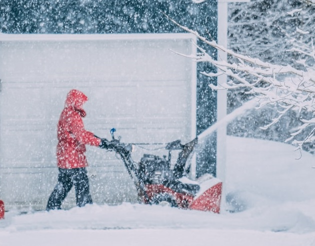 Man using snowplow in front of home
