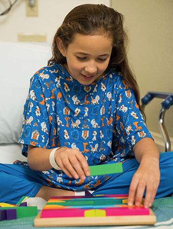 A little girl in a hospital bed plays with a toy that involves a board with blocks of different shapes.