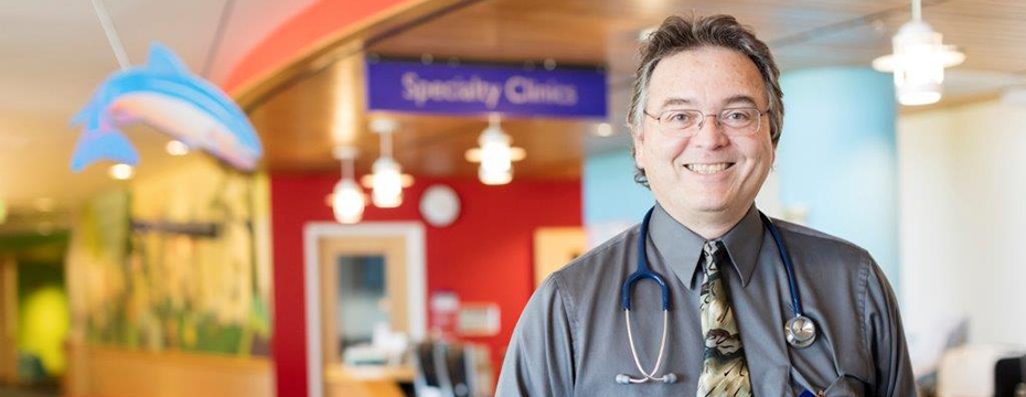 "A doctor smiling in a clinic lobby with a sign reading ""Specialty Clinics"" in the background."