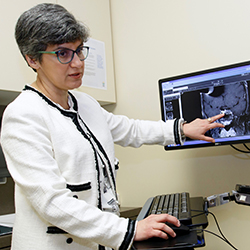 Dr. Maria Fleseriu in a clinic pointing at a monitor with an imaging test