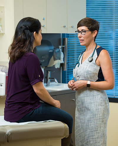 Dr. Laurel Hallock-Koppelman, OHSU family practitioner, talks with a patient in a clinical office