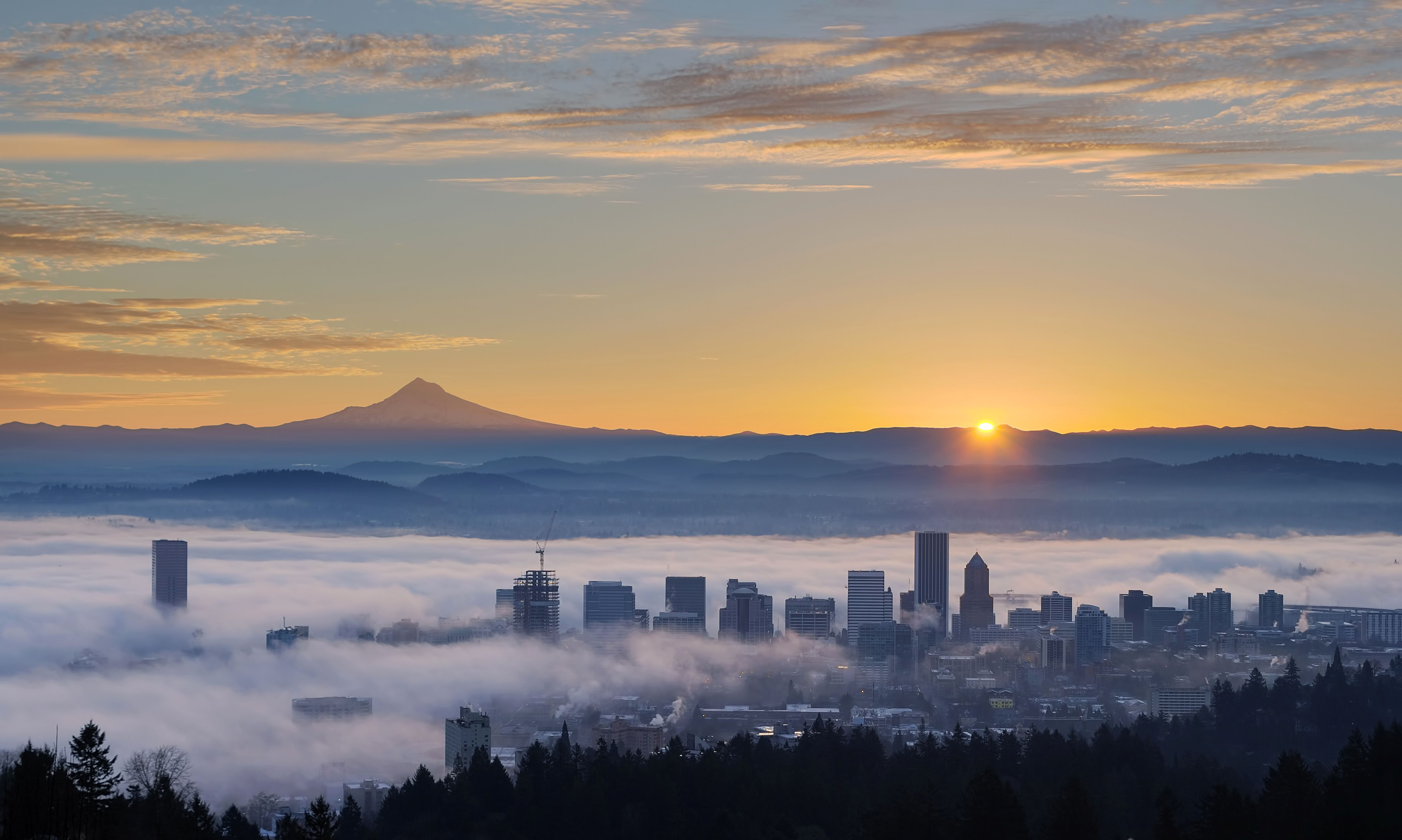 Sunrise view of downtown Portland, OR covered in fog with Mt. Hood in the background.