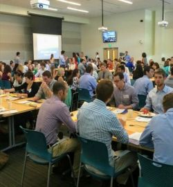 Fifty or more people seated and standing in a learning studio discussing innovation topics with their teams.