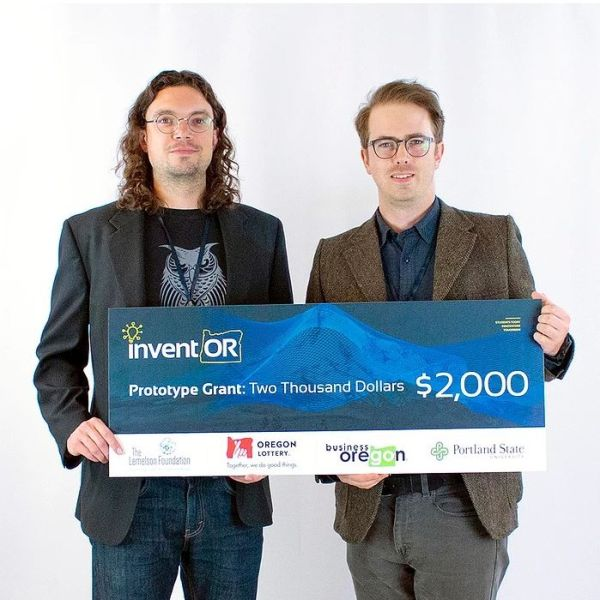 Two graduate students holding a $2,000 check for winning the InventOR competition.