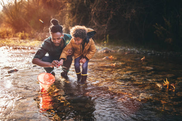 Man with child enjoying net fishing together in a stream