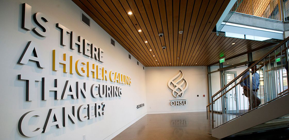 "An interior shot of inside the OHSU Knight Cancer Research Building, showing a wall that has the OHSU logo on it, with the words ""Is there a higher calling than curing cancer?"" next to it."