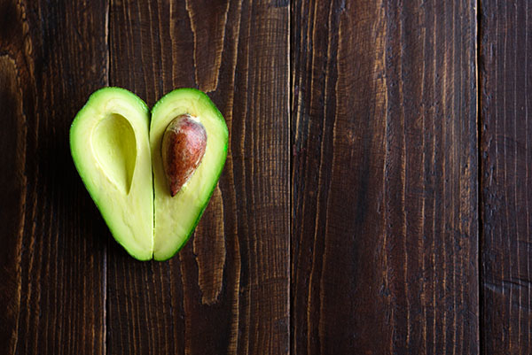 Avocado cut open and arranged in heart shape on wooden surface