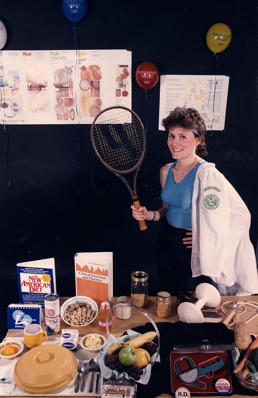 Teresa Jones, dietetic intern, poses with dietetic-related items, circa 1980s