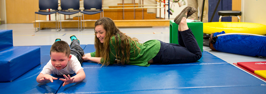A female physical therapist guiding a young boy through physical therapy exercises on a mat.