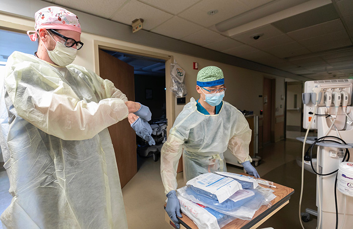 Dr. Jordan Young (left) and Dr. Ran Ran put on protective gear before entering a patient room in OHSU's Emergency Department.