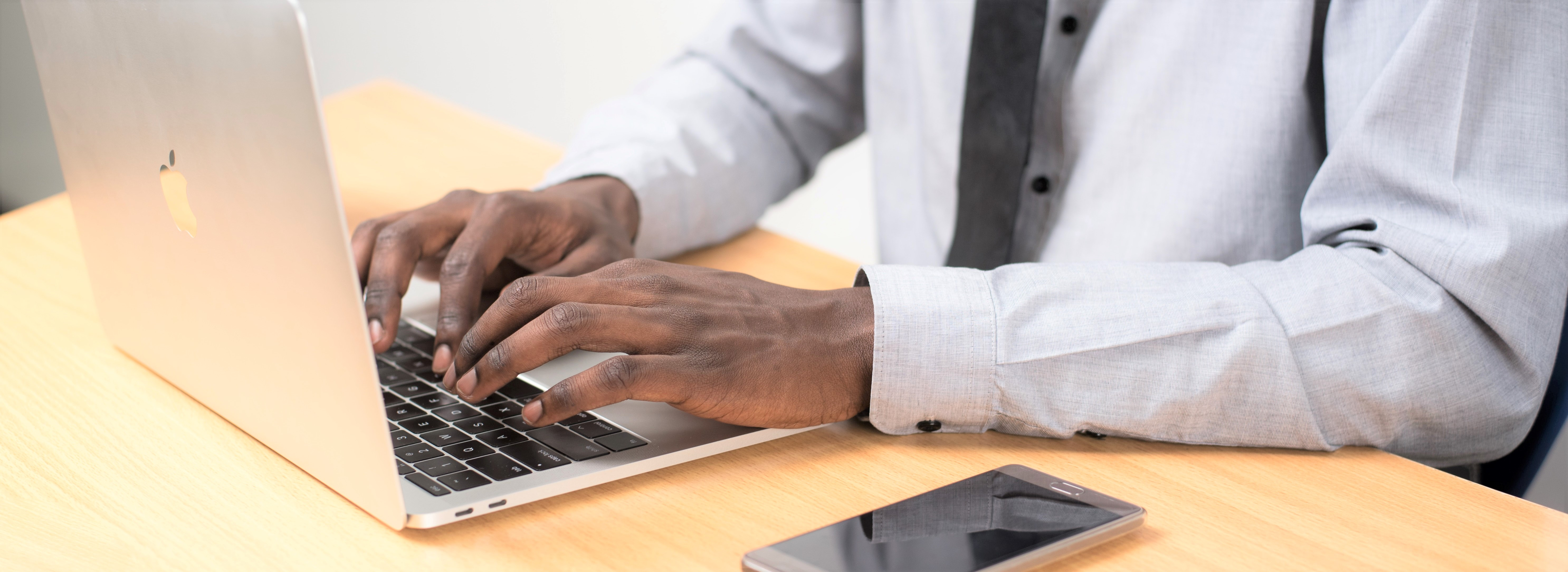 Person types on laptop wearing a button down and tie