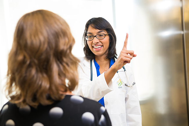 Dr. Hetal Choxi pointing her finger and having a female patient follow the finger with her eyes as part of an exam.