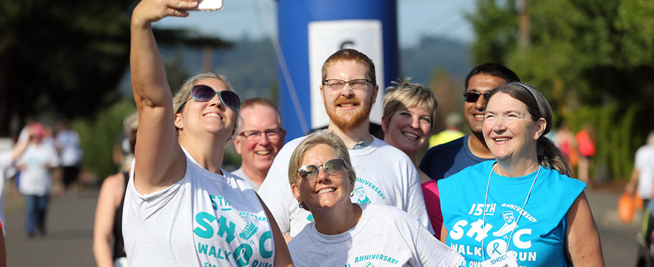 A group of people stopping to pose for a selfie while participating in a fundraising walk.
