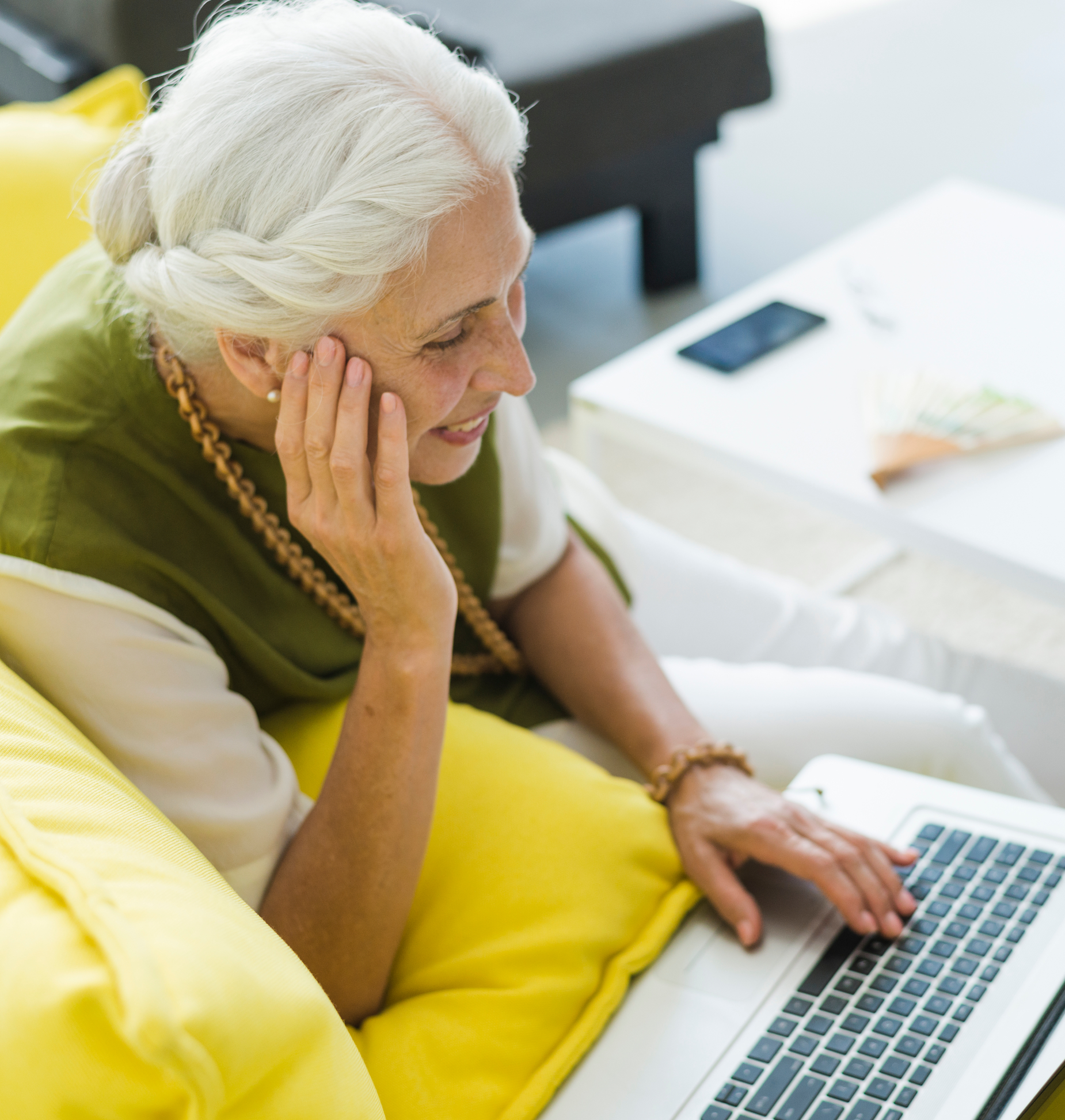 Older woman uses laptop while relaxing on the couch at home