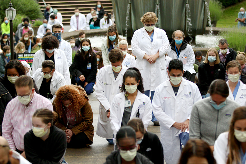 OHSU researchers, scientists and clinicians in white lab coats, many kneeling, heads bowed, wearing protective face masks