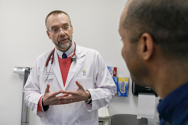Dr. Tomasz Beer speaking with a patient in an exam room.