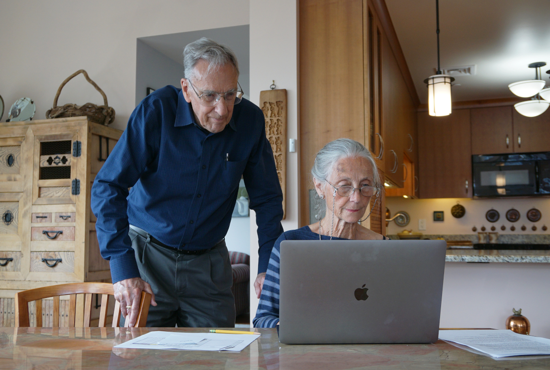 Two older adults look at their computer in the living room of their apartment