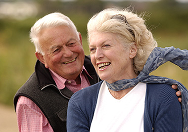 An older couple outdoors, smiling