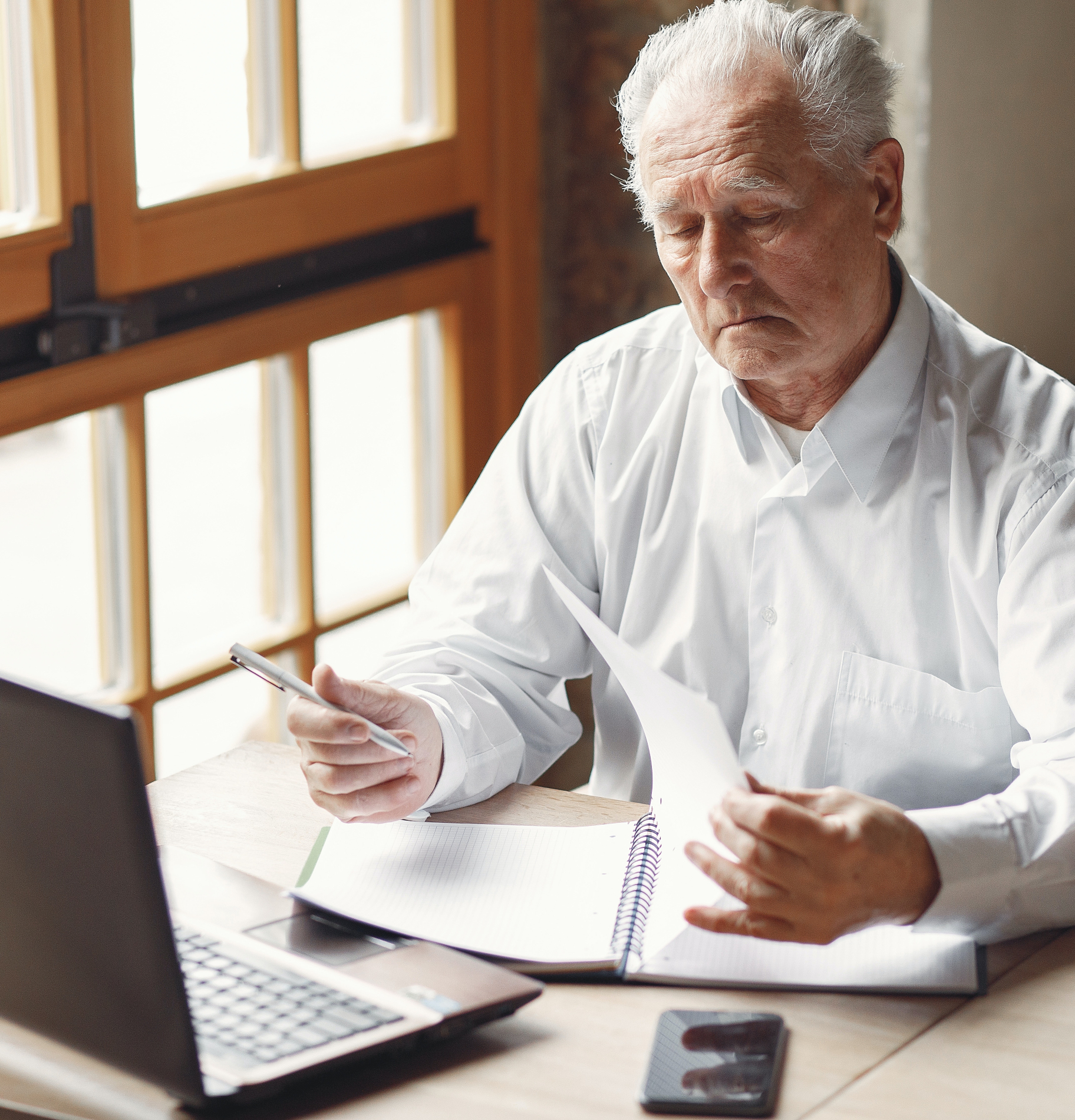 Elderly man works on a computer at home with a notebook