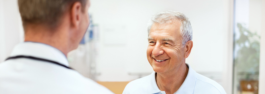 An older man smiling while speaking with another man, who is his doctor.