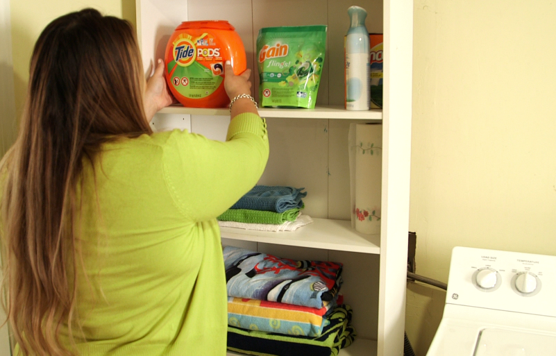 A woman stores laundry packets on a high shelf up an away and out of reach of children
