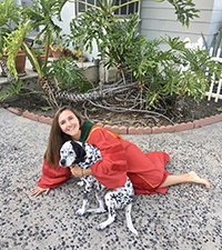 A woman in her graduation gown lying on the ground hugging her dog.