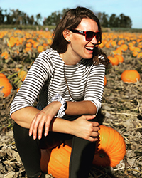 A woman smiling sitting on a pumpkin in a pumpkin patch on a sunny day.