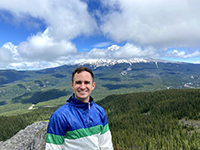 A man smiling while on a hike with mountains and hillsides in the background.