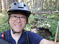 A photo of Bill Chang wearing a helmet on a forest trail.