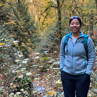 A woman smiling while on a hike in the woods.