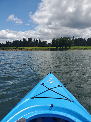 A POV photo inside a kayak looking out on a lake.