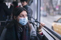 Photo of a person wearing a mask on public transportation